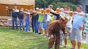 line of guys standing on grass holding a glass of beer at arms reach