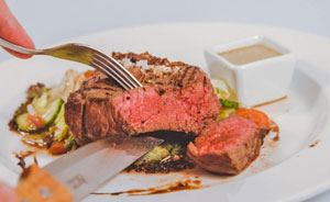 steak cooked medium being cut on a plate
