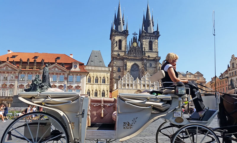 prague horse and carriage on the old town square with Church of Our Lady Before Tyn in the background