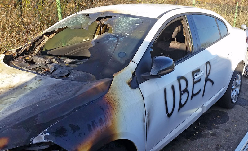 Burned out car with uber written on the door