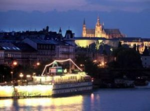 prague boat hotel admiral lit at night with prague castle in background