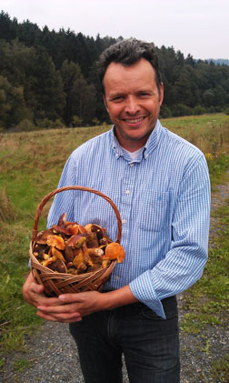 man with basket of mushrooms standing in a field
