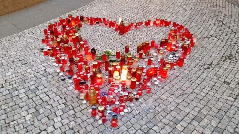 candles on cobbled pavement in the shape of a heart
