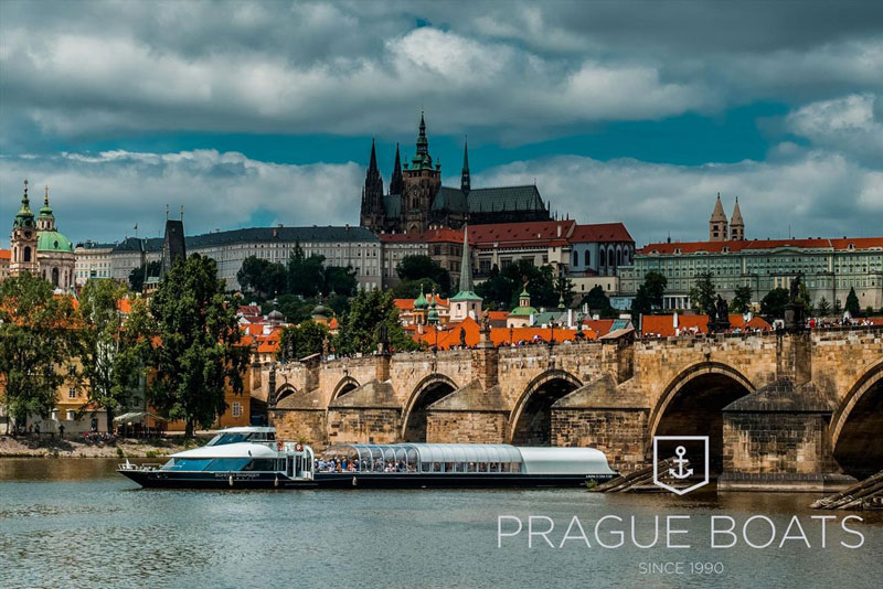 tour boat on the river vltava with the gothic stone charles bridge and prague castle in background