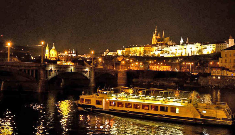 tour boat on the river vltava at night with prague castle lit in background