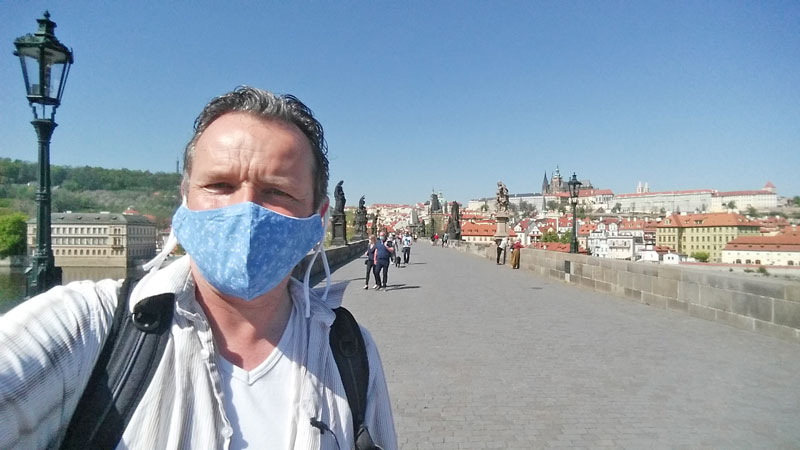 man standing on charles bridge in prague with mask