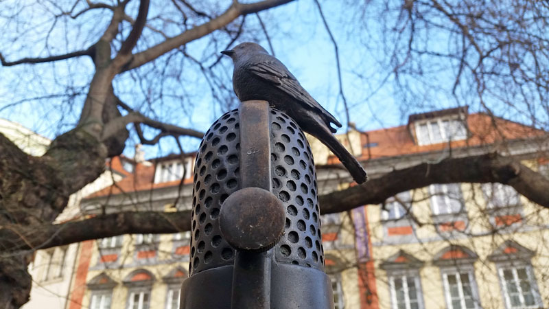Milada Horakova memorial in prague bird perched on microphone