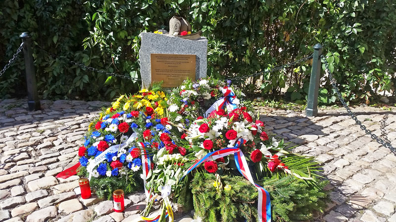 prague new york firefighters memorial. granite stone with plaque, helmet with the number 114 and flowers on a 9/11 anniversary