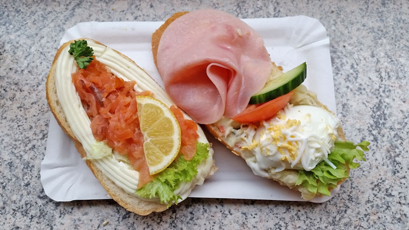two open czech sandwiches. One is ham and egg, the other is smoked salmone