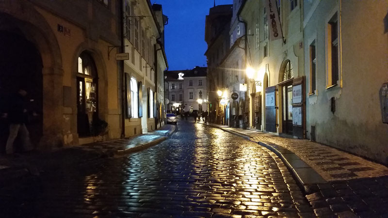 a wet cobble stone road in prague reflecting light from a street lamp
