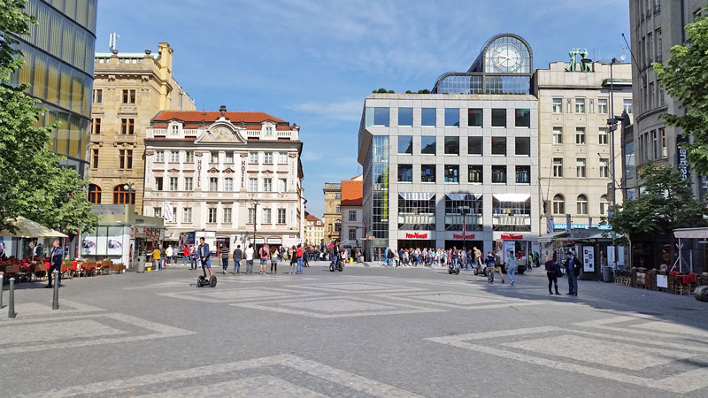 the pedestrianised bottom of wenceslas square in prague with black and white cobbles. a mix of modern and old stylle buildings