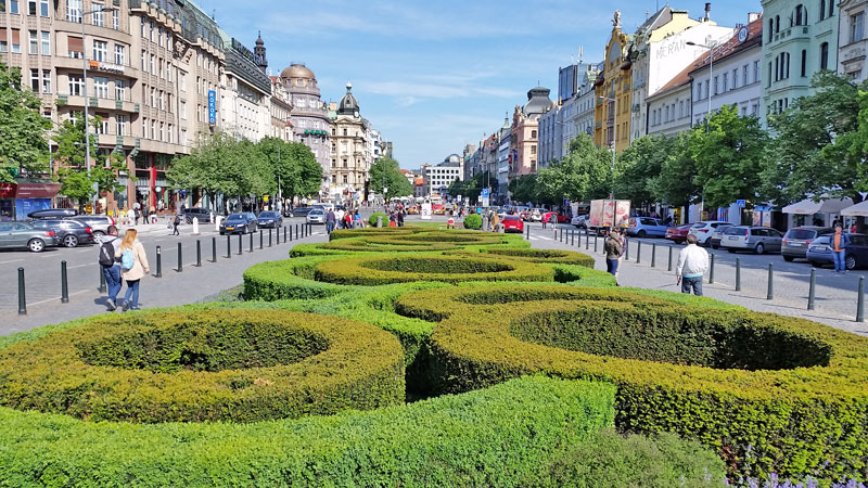 prague wenceslas square looking down the square with roads on both sides and in the centre stretching away are shaped privet hedges forming curves and circles