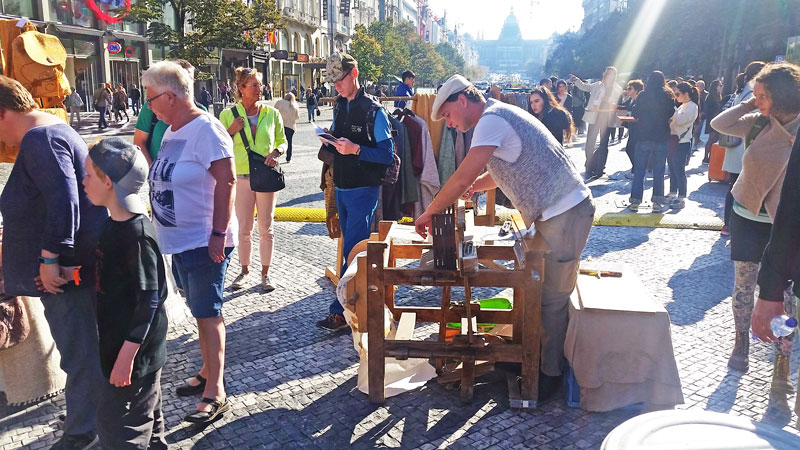 a man with a white flat cap operating a manual thredding machine at the bottom of wenceslas square. Far in the distance is the national museum