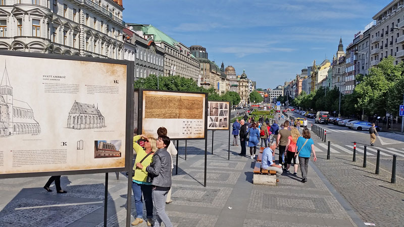 people looking at boards on wenceslas square showing the history of the area