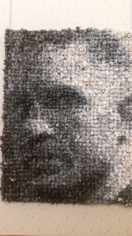 thousands of screwed up magazine pages make a black and white image of a mans face that can only be seen through a camera or by covering one eye.