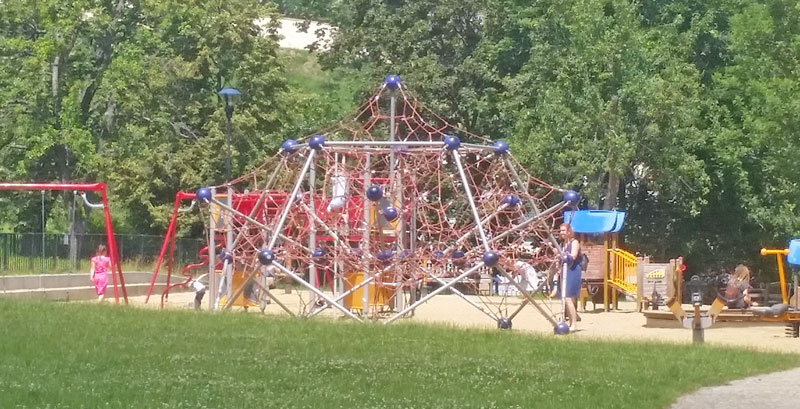 childrens playground in prague with rope climbing frame with sandy ground,  grass in foreground and trees in background