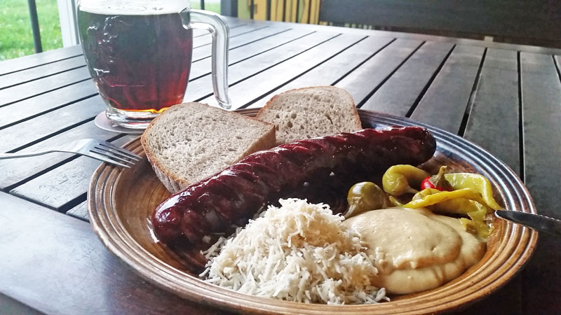 grilled czech sausage on a plate with slices of bread, horseradish, czech mustard and peppers. The plate is on a table and there is a glass of beer next to it