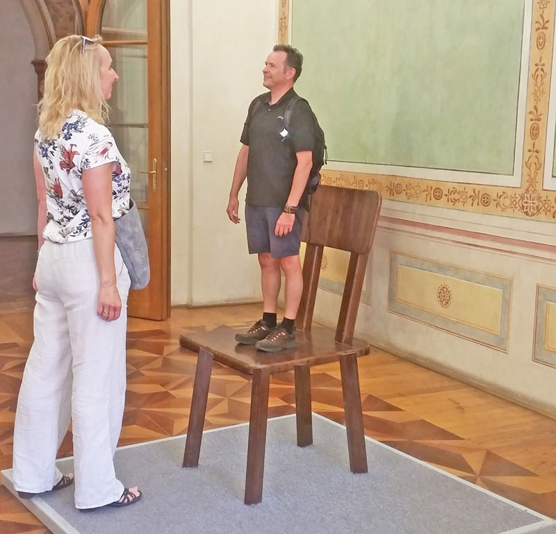an exhibit at the prague illusion art museum that shows a man and a woman facing each other but the man appears much smaller