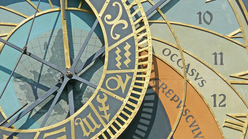 a detail photo of the prague astronomical clock showing the 12 hour day division, roman numerals painted in gold and a wheel shoeing astrological signs