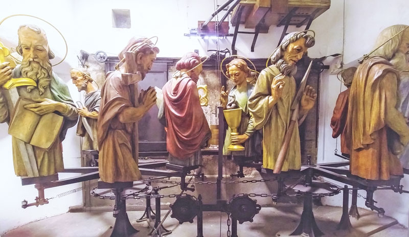 8 out of 12 wooden busts of apostles set on metal spindles pulled by chains and turned by springs, the view from the inside of the prague astronomical clock