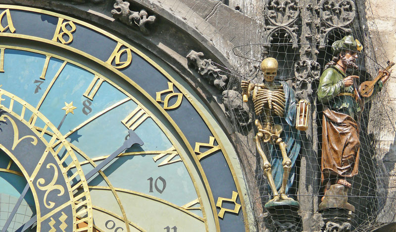 a skeleton pulling a rope in his right hand and holding an hourglass in his left