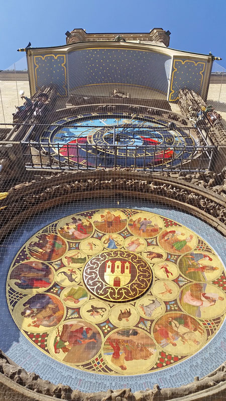 the view looking up at the prague astronomical clock with the golden coloured calendarium at the bottom, then the largely blue astronomical clock and then the rest of the old town hall tower