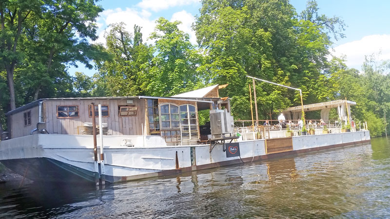 bobs bbq floating barge in prague moored against the tree covered shooters island