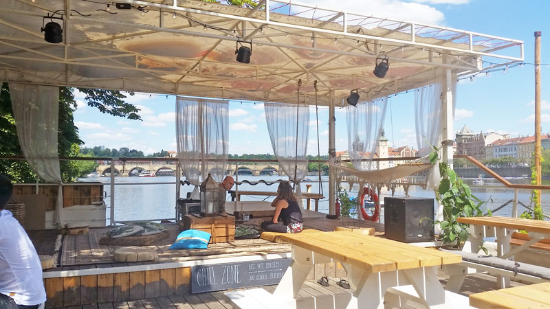 the rear of bobs bbq floating barge in prague with low seating area and see through drapes with a view of the river vltava and charles bridge