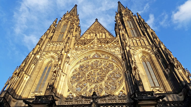 the west entry t the gothic st vitus cathedral in prague showing two pinnacled towers either side of a rose window