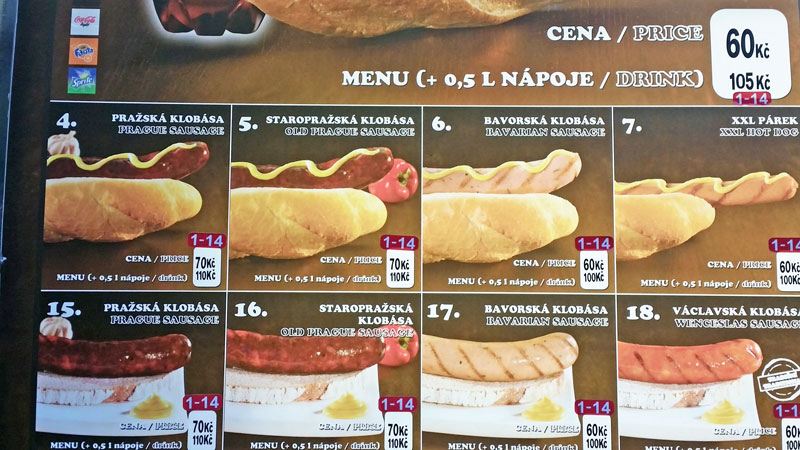 prague hot dogs menu board showing pictures of hot dogs served in long rolls or with sliced bread