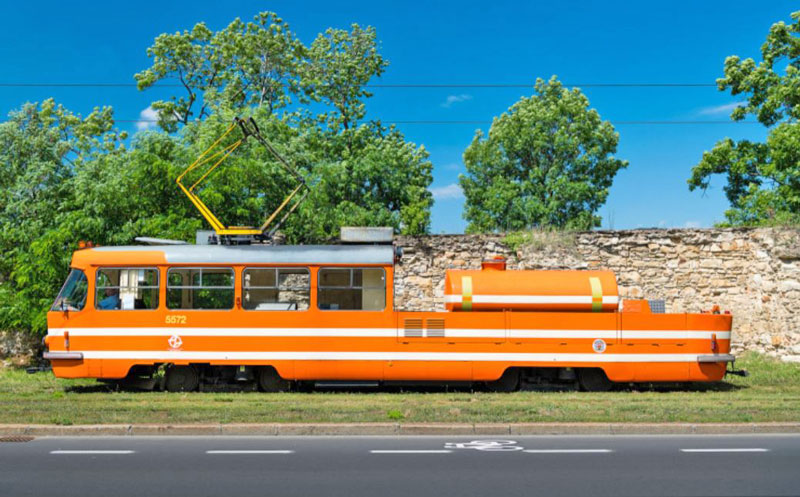 the prague lubrication tram, orange with white stripes, a rough stone wall behind, trees and blue sky