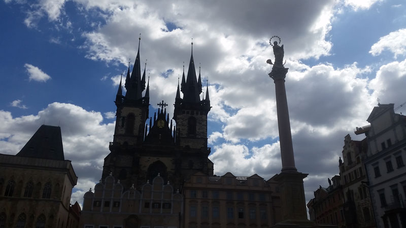 silhouette against a blue sky with white clouds of the prague marian column and the tyn church