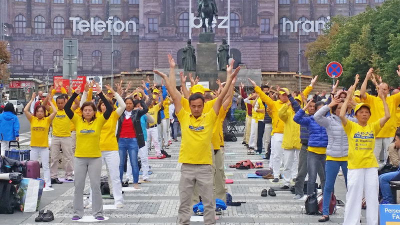 falun gong members in yellow t-shirts protest and exercise at the top of wenceslas square in prague. they are standing on black and white cobbles forming concentric squares