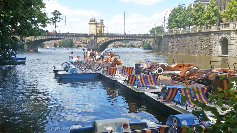 boats and prague pedalos moored on the river vltava with legion bridge in the background
