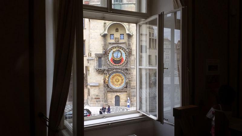 prague astronomical clock seen through a window of a building opposite