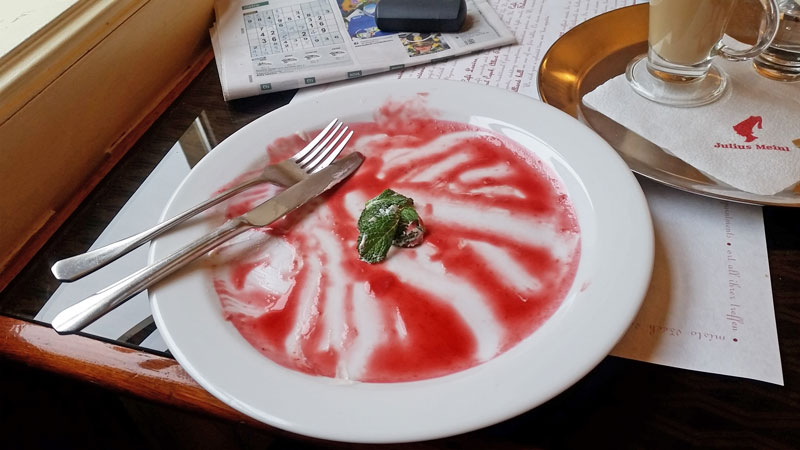 white plate with leftovers of raspberry sauce and a sprig of mint with knife and fork