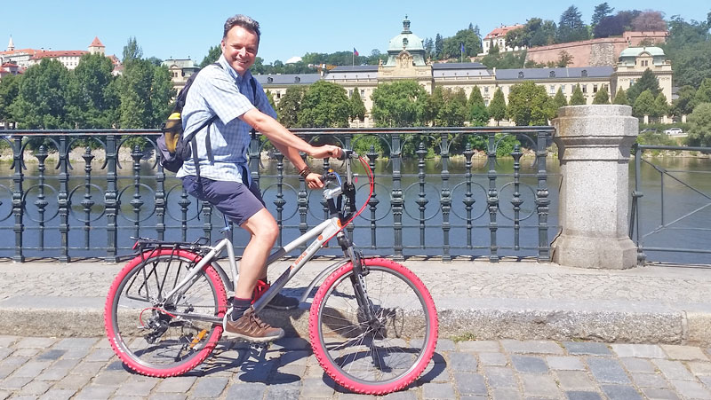 man on bike with red tyres next to riverside in prague