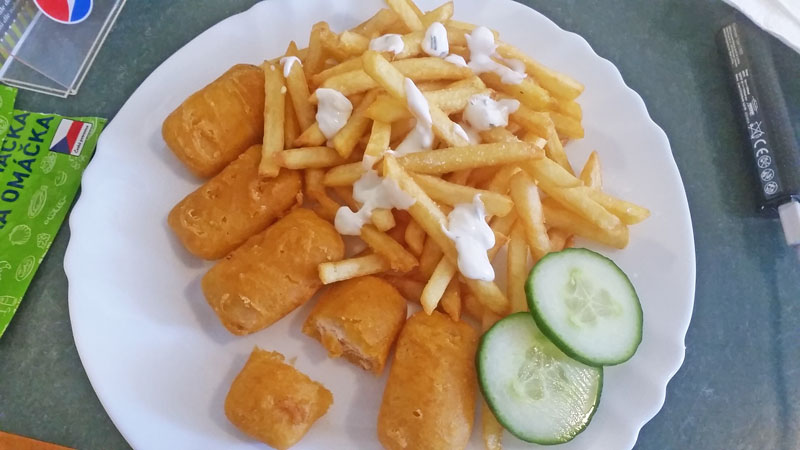 5 fried salmon nuggets served with chips, tartar sauce and two slices of cucumber
