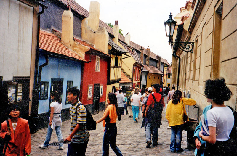 very narrow cobbled street with small houses on the left single floor and two floor brightly colured houses with chimneys