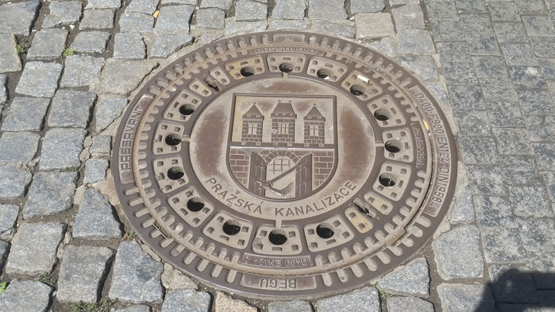 prague lesser coat of arms on an iron drain cover
