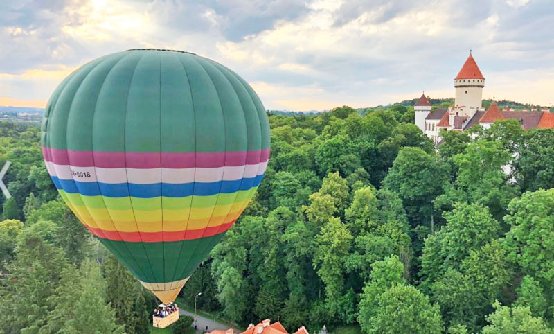 rainbow coloured prague hot air balloon over a forest and passing a castle at low level