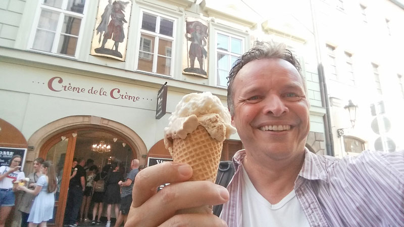 man with prague ice cream gelato in a cone standing outside an historic building with period decoration