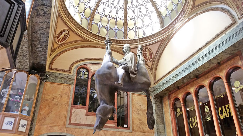 sculpture of a king sitting on the belly of an upside-down horse which has it's feet tied and is hanging from the ceiling.