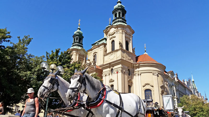 twin towers of the baroque church of st nicholas in prague old town with horses and carriage and blue sky