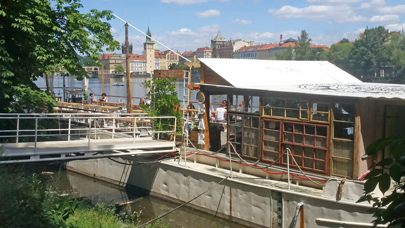 white restaurant barge moored on the river next to shooters island in prague
