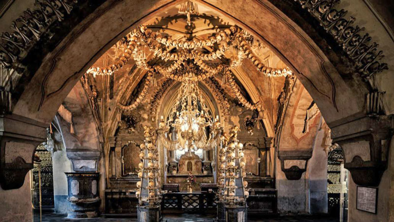 sedlec ossuary chapel with thousands of bones arranged in pyramids, chandeliers and coats of arms
