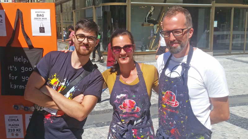 two men and a woman with paint splattered aprons