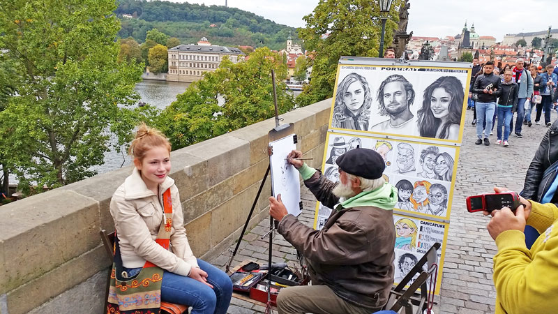prague charles bridge portrait artist drawing a caricature of a young girl with ginger hair