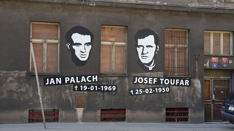 faces of jan palach and josef toufar on a wall with the dates of their death