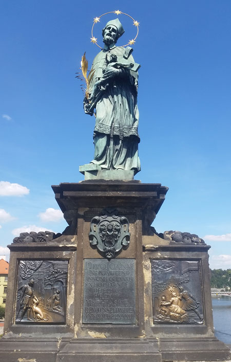 prague jan nepomuk statue in 2020 with both brass plaques now shiny and the statue is now oxidised to a green colour